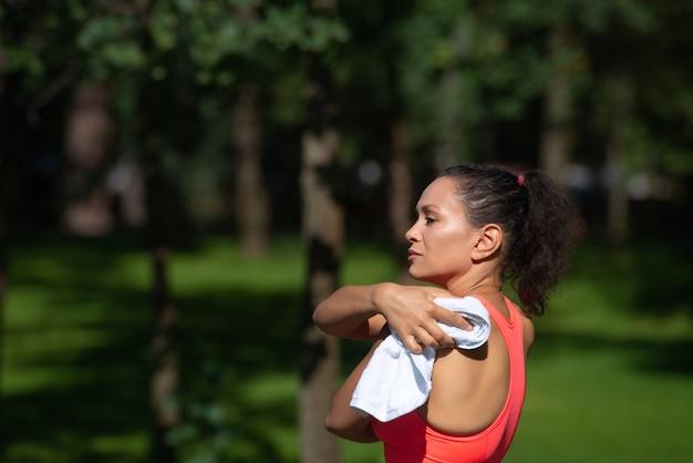 運動トレーニング後に汗を拭く疲れた若い女性の側面の肖像画