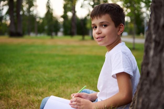 ハンサムな小学生の賢い男の子の学生、宿題をしているインテリジェントな男子生徒、数学の課題を解決し、屋外で勉強を楽しんで、カメラにかわいい笑顔の横向きの肖像画。子供は学校に戻ります