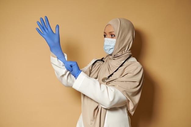 コピースペースとベージュの表面で正面の前にポーズをとって医療用保護手袋を着用しているヒジャーブのイスラム教徒の女性医師の側面の肖像画