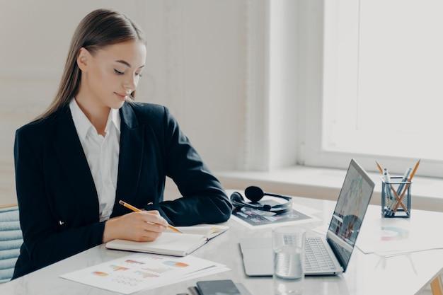 Боковой портрет улыбающейся сконцентрированной молодой кавказской деловой женщины в черном формальном костюме, пишущей в записной книжке, сидя за большим белым столом с окном на светлом минималистичном фоне.