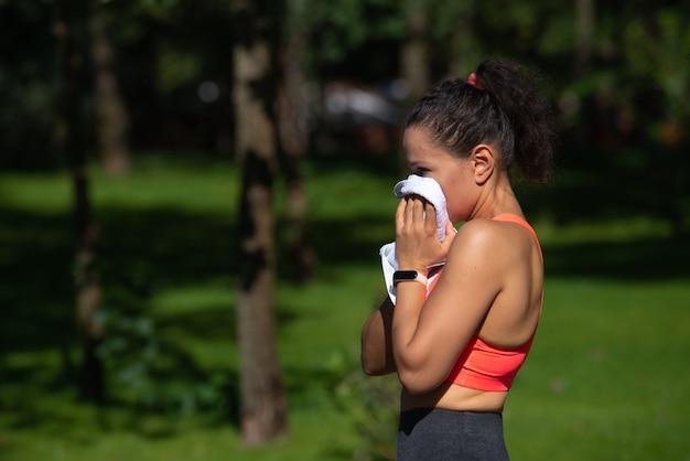 都市公園での運動トレーニングの後に彼女の汗を拭く疲れた若い女性の側面の肖像画。屋外でのカーディオトレーニングのコンセプト