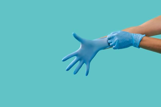 青い背景に分離された青い医療用保護滅菌ラテックス手袋を着用して認識できない人の手の側面の肖像画