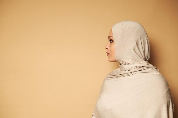厳格な宗教的な服を着た若いアラブのイスラム教徒の女性の側面の肖像画と側面を見てヒジャーブで覆われた頭