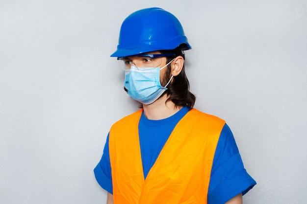 コロナウイルスとcovid-19に対する医療マスクを持つ若い建設労働者の側面の肖像画 Premium写真
