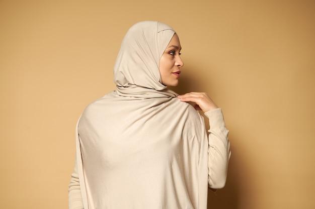 コピースペースでベージュの表面に対して横を向いている若い穏やかなイスラム教徒の女性の側面の肖像画