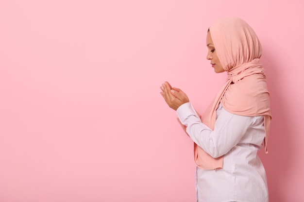 Side portrait of a serene muslim arab woman in pink hijab and strict outfit praying, performing namaz, isolated on colored background with space for text