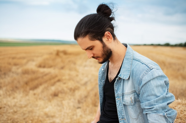 Side portrait of young guy in denim jacket with ponytail hairstyle in hay field.