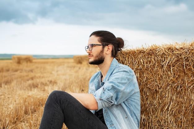 Side portrait of young guy in farm field sitting near haystacks.