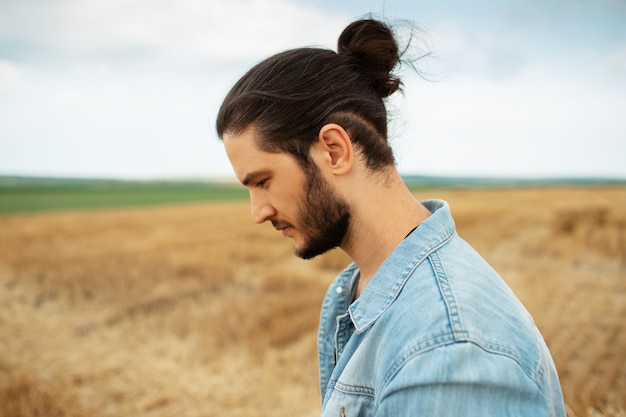 Side portrait of young hipster in denim jacket with ponytail hairstyle.