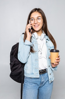 Side portrait of young student woman talk to smartphone, holding coffee to go cup isolated on gray wall