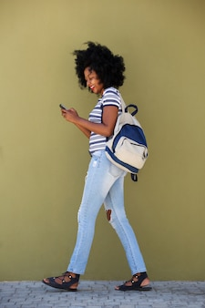Side portrait of young woman walking with bag and smart phone