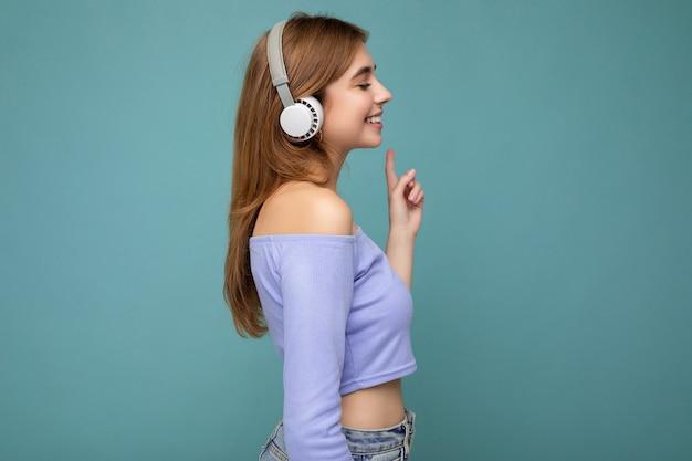 横顔青いクロップ トップを着ている美しい肯定的な笑顔の若いブロンドの女性