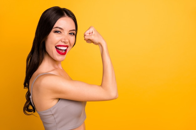 Side profile close up photo of cheerful strong powerful woman demonstrating her triceps elbow near empty space with lips pomaded isolated vivid color background