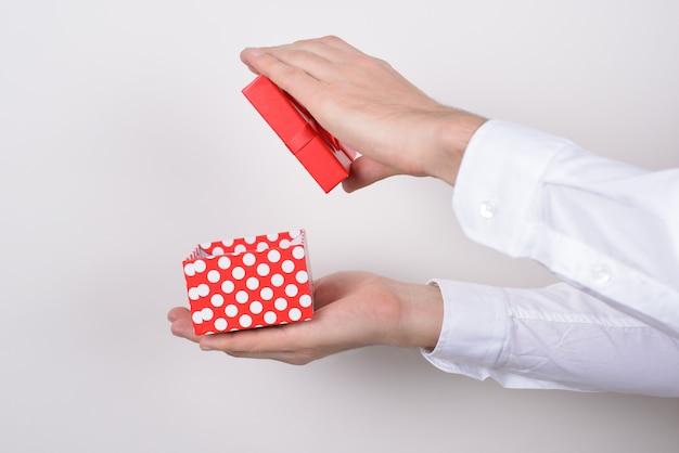 측면 프로필은 회색 배경에서 분리된 손에 열린 포장 풀기 선물 상자를 들고 있는 손의 사진 초상화를 닫습니다.