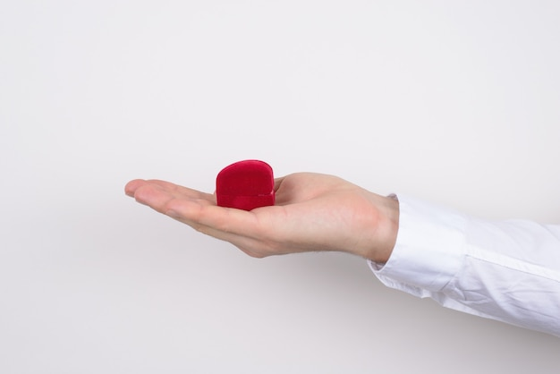 Side profile closeup cropped photo of hand holding open unpacked unwrap red heart shaped small little box with ring inside isolated grey background