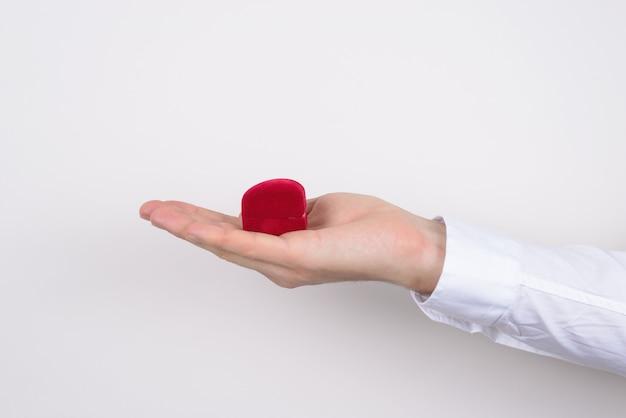 Боковой профиль крупным планом обрезанное фото руки, держащей открытую распакованную распакованную красную коробочку в форме сердца с кольцом внутри изолированного серого фона