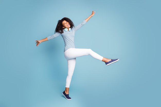 Side profile full length body size photo of cheerful positive pretty sweet girlfriend dancing jumping with eyes closed isolated blue pastel color background
