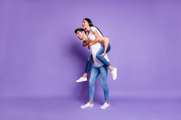 쾌활한 긍정적 인 귀여운 피기 백 커플의 측면 프로필 전체 길이 몸 크기 사진 여자를 들고 남자와 티셔츠 데님에 이빨 격리 된 파스텔 바이올렛 컬러 배경