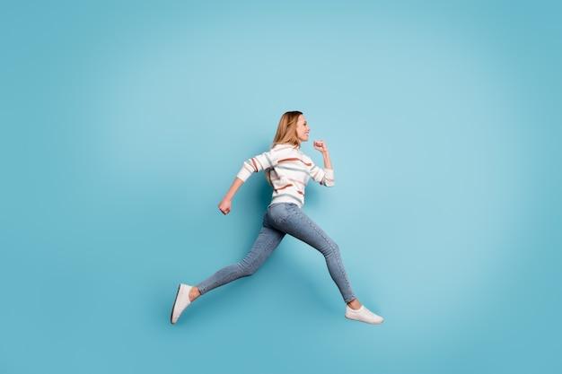 Боковой профиль в полный рост, фото веселой позитивной симпатичной подруги, зубасто улыбающейся в джинсах, джинсовая ткань, бег, прыжки, изолированная пастельно-синяя стена