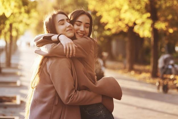 Боковой профиль молодой симпатичной улыбающейся брюнетки-близнеца обнимает и веселится в повседневном пальто, стоящем рядом друг с другом на осенней солнечной парковой аллее на размытом фоне.