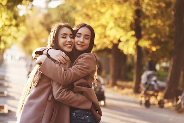 Боковой профиль молодых улыбающихся брюнеток-близнецов, обнимающих и веселых в повседневном пальто, стоящих рядом друг с другом на осенней солнечной парковой аллее на размытом фоне.