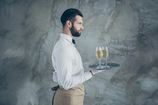 Боковое фото профиля привлекательного сервера, держащего поднос с бокалами шампанского с изолированной щетиной серой бетонной стеной