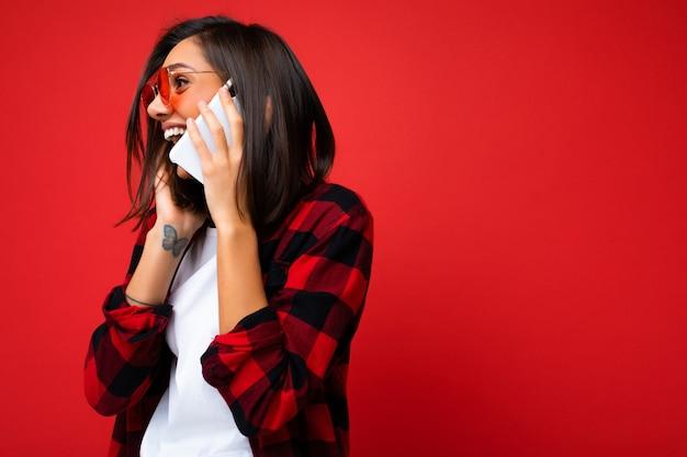 スタイリッシュな赤いシャツ白いtシャツと赤いサングラスを身に着けている美しいポジティブな若いブルネットの女性の横顔の写真は、横を向いて携帯電話で話している赤い背景の上に分離されました