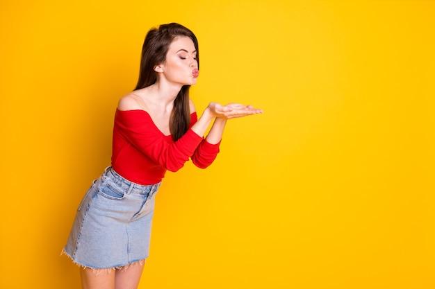 매력적인 사랑스러운 어린 소녀의 측면 프로필 사진은 눈을 감고 공기 키스를 보낸 잘생긴 남자 셔츠를 입고 어깨를 덮지 않은 데님 미니 스커트를 입고 선명한 노란색 배경을 격리했습니다.
