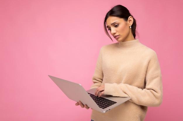 Боковое фото профиля очаровательной довольно грустной молодой леди, держащей ноутбук, изолированной на фоне стены