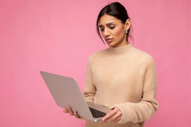Netbook에서 아래를 내려다 보면서 벽 위에 절연 노트북을 들고 매력적인 꽤 슬픈 젊은 아가씨의 측면 프로필 사진.
