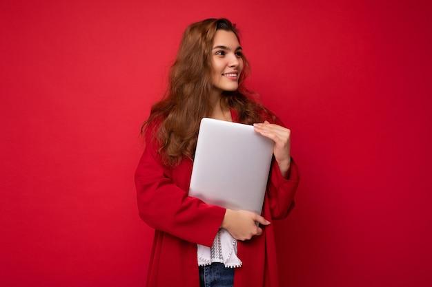 Боковое фото профиля очаровательной милой молодой леди, держащей ноутбук, изолированную на фоне стены. копировать пространство