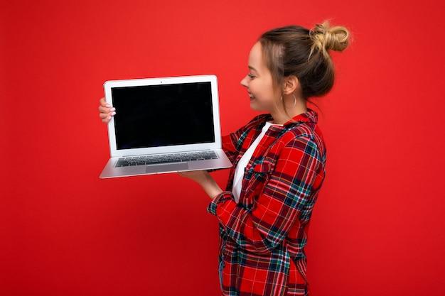 빨간 셔츠를 입고 화면을 보고 있는 넷북을 들고 있는 매력적인 예쁜 젊은 여성의 측면 프로필 사진