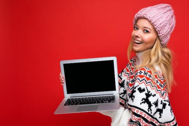 Боковое фото профиля очаровательной улыбающейся счастливой симпатичной молодой девушки, держащей ноутбук, изолированную на фоне стены, в зимней одежде. макет, скопируйте пространство