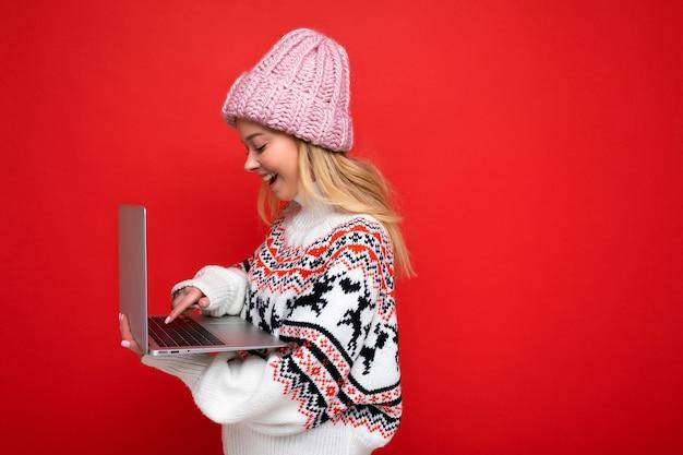 Боковое фото профиля очаровательной улыбающейся счастливой симпатичной молодой леди, держащей ноутбук, изолированной на красном фоне стены, смотрящей на экран монитора в зимней шапке и вязаном новогоднем свитере.