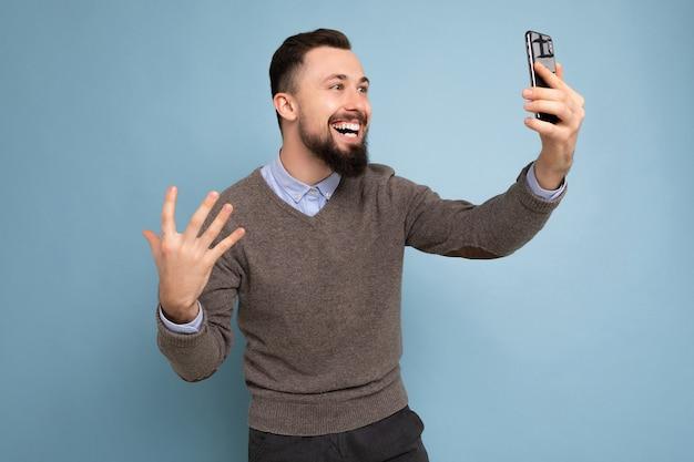 캐주얼 회색을 입고 수염을 가진 긍정적 인 잘 생긴 젊은 갈색 머리 형태가 이루어지지 않은 남자의 측면 프로필 사진