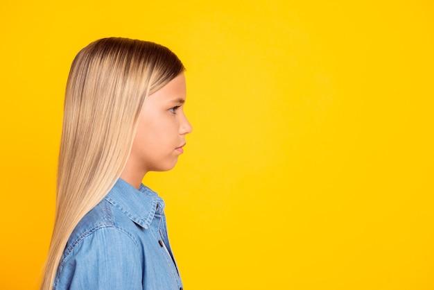 선명한 노란색 배경에서 격리된 빈 공간을 바라보는 데님 셔츠를 입은 꽤 진지하고 차분한 소녀의 측면 프로필 사진