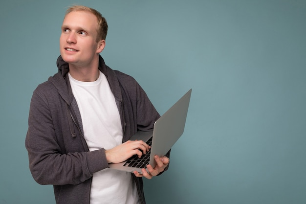 Side profile photo shot of handsome blonde man holding computer laptop typing on keyboard having an