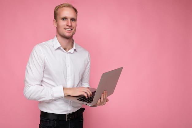 Боковой профиль фото выстрел красивого улыбающегося уверенно белокурого взрослого человека мужского пола, держащего компьютерный ноутбук, набрав на клавиатуре в белой рубашке, глядя на камеру, изолированную на розовом фоне.