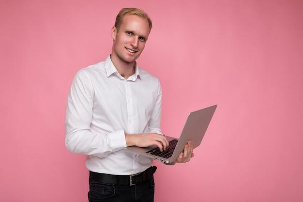 Боковой профиль фото выстрел красивого улыбающегося счастливого уверенного блондинки, держащего и использующего компьютерный ноутбук, печатающего на клавиатуре в белой рубашке, смотрящего на камеру, изолированную на розовом фоне.