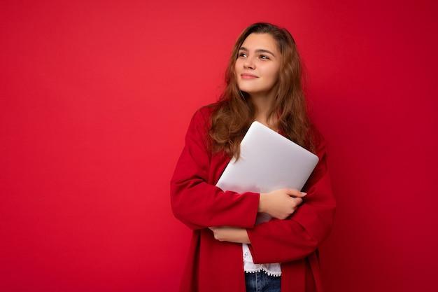 Боковой профиль портрет выстрел загадочного красивая молодая темные волосы вьющиеся женщины, держащей закрыть ноутбук, носить красный кардиган и белую блузку, глядя в сторону, изолированные на красном фоне.