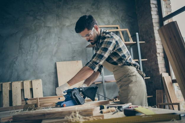 Side profile  serious pensive confident man processing wood with sander machine with eyes protected eye wear in checkered shirt gloves
