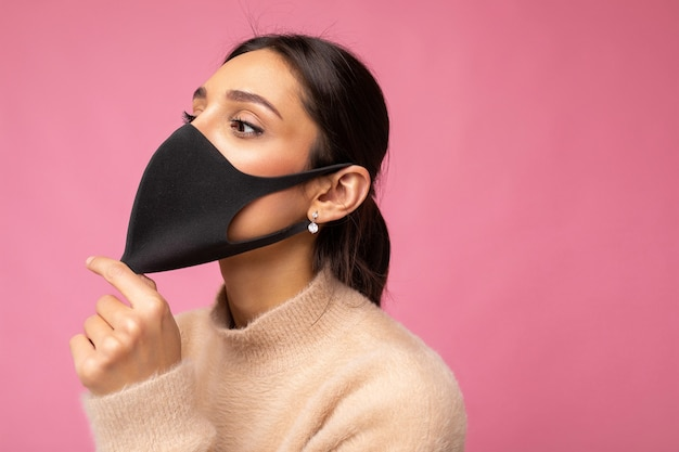 Side-profile shot of young woman wearing an anti-virus protection mask