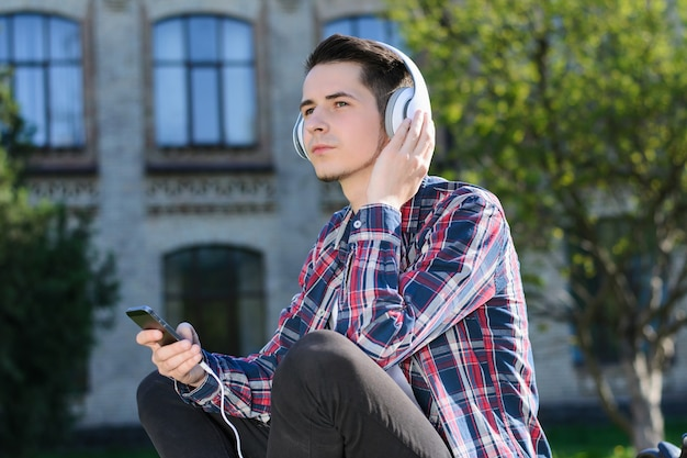 Side profile turned photo of concentrated guy enjoying cool clear sound from his new headset sitting on grass