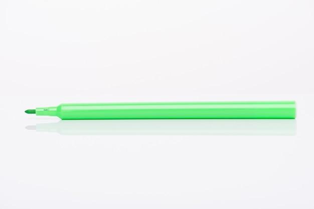 흰색 배경에 분리된 모자가 있는 밝고 생생한 밝은 녹색 마커의 측면 프로필 보기 클로즈업 사진