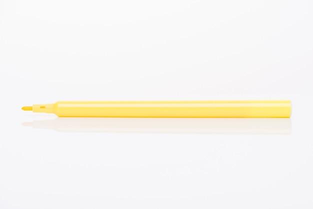흰색 배경에 분리된 모자가 있는 밝은 노란색 마커의 측면 프로필 보기 클로즈업 사진