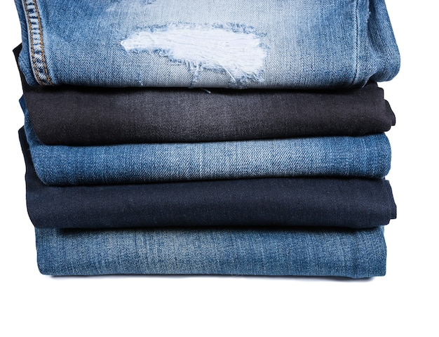 Side profile view of different types of blue jeans folded and stacked on white background, five denim jeans of varying color washes and styles