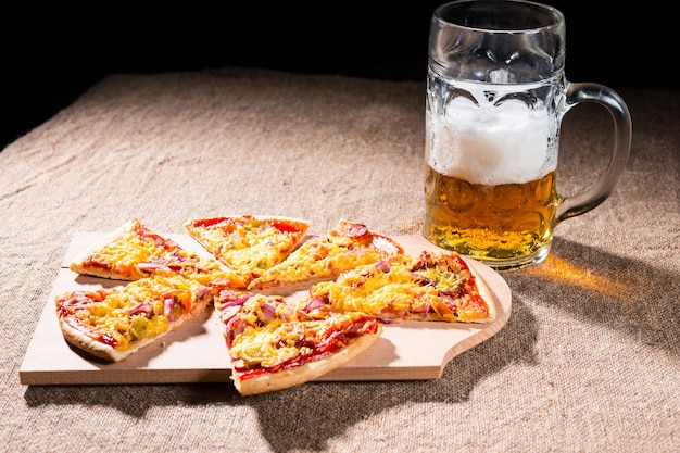 Side profile view of mug of beer with frothy head beside slices of pizza arranged on wooden cutting board on burlap covered table surface