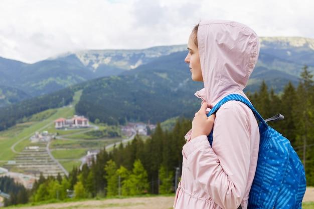 カジュアルなバラのジャケットと青いリュックサック、女性のバックパッキングと放浪を身に着けている魅力的な美しい少女の側面図