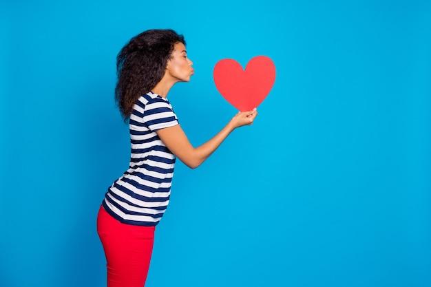 큰 붉은 마음을 키스하는 부드러운 여자의 측면 프로필보기