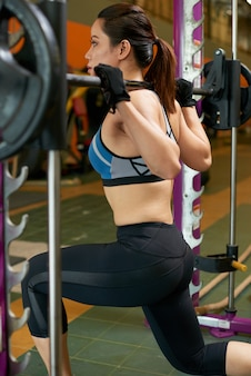 Side rear view of fit woman training with heavy weight on smith machine